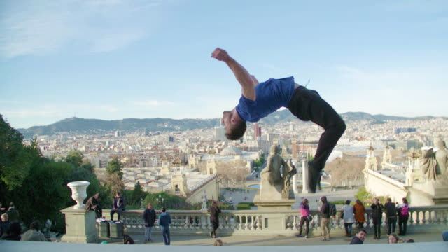 man backflipping with barcelona skyline on the background - city break stock videos and b-roll footage