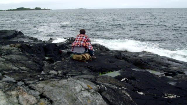 man backpacker traveler rests on the rocky shore. drone point of view - one man only stock videos & royalty-free footage