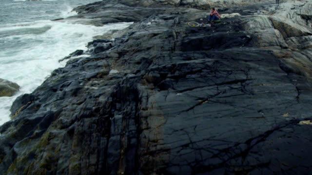 Mann Backpacker Reisenden liegt auf der felsigen Küste. Drohne Sicht