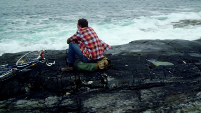 vidéos et rushes de voyageur routard homme repose sur la côte rocheuse. point de vue de drone - assis