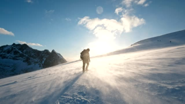 Man backpacker trekking through storm in mountains at sunset