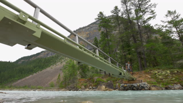 a man backpacking and hiking on a bridge over a river. - time-lapse - rocky mountains stock videos & royalty-free footage