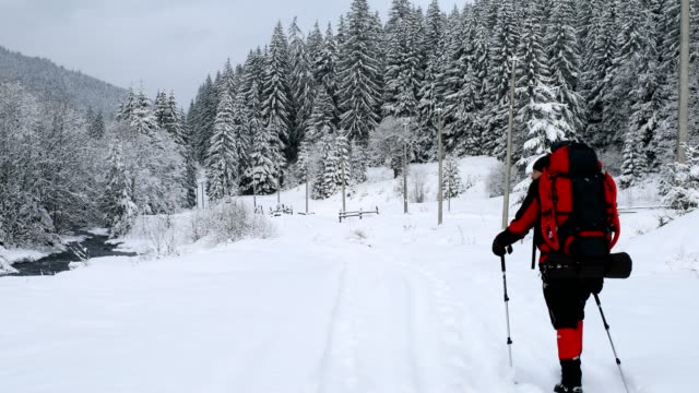 Man backpacking in winter forest