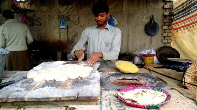man baking flatbread in a traditional mud oven - bread stock videos & royalty-free footage