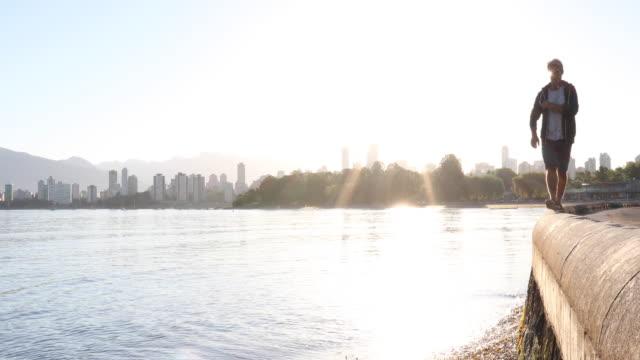 Man balances above calm ocean bay at sunrise, city behind