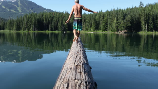 man balances on floating log, mountain lake - semi dress stock videos & royalty-free footage