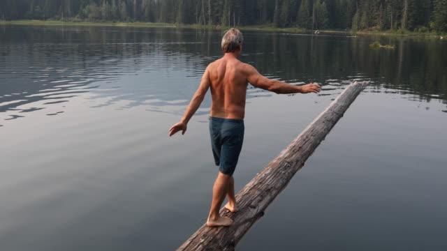 man balances while walking along log, mountain lake - 中年の男性だけ点の映像素材/bロール