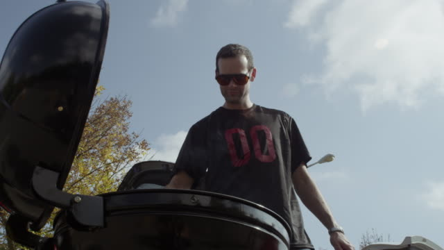 Man barbecuing in sports jersey