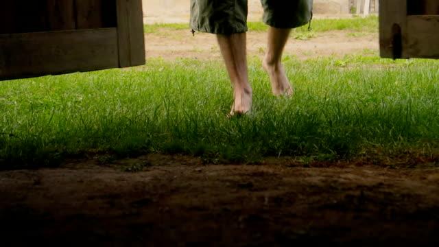 vidéos et rushes de l'homme aux pieds nus entrer / venir au garage avec sol en terre battue et l'herbe verte - short