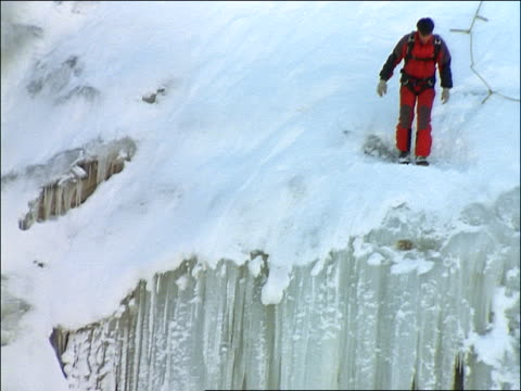 man base jumping off edge of icy cliff - cliff stock videos & royalty-free footage