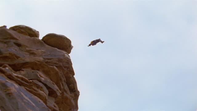 LA, TD, HA, Man base jumping off rock formation, Moab, Utah, USA