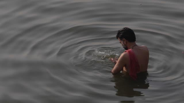 ms ha man bathing in ganges river / varanasi, india - スピリチュアル点の映像素材/bロール