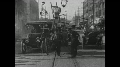 1915 man beats charlie chaplin like horse as chaplin pulls cart through city traffic - slapstick comedy stock videos & royalty-free footage