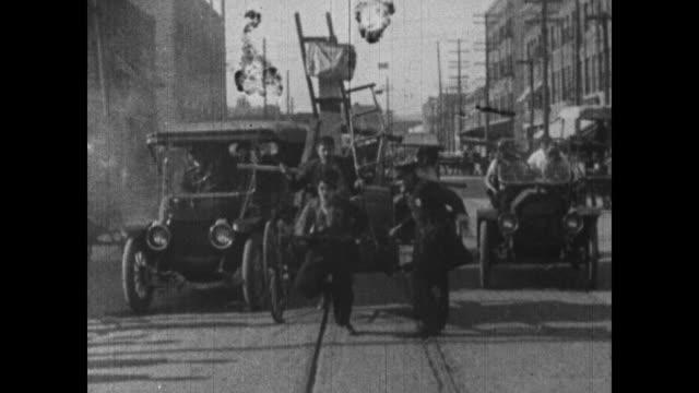 vídeos de stock, filmes e b-roll de 1915 man beats charlie chaplin like horse as chaplin pulls cart through city traffic - charlie chaplin
