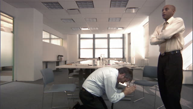 man begging on knees in front of another man in conference room / standing man leaving room / pleading man following on knees - kneeling stock videos and b-roll footage