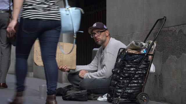 man begs for money on wall street at the peak of the morning commuter rush / he sits next to a small cart holding his possesssions and holds a... - crisi video stock e b–roll