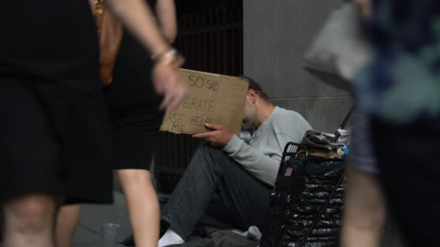 vídeos de stock, filmes e b-roll de a man begs for money on wall street at the peak of the morning commuter rush / he sits next to a small cart holding his possesssions and holds a... - pedindo esmola