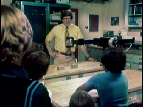 1976 WS Man behind mechanical arm talking to young students about robots / United States