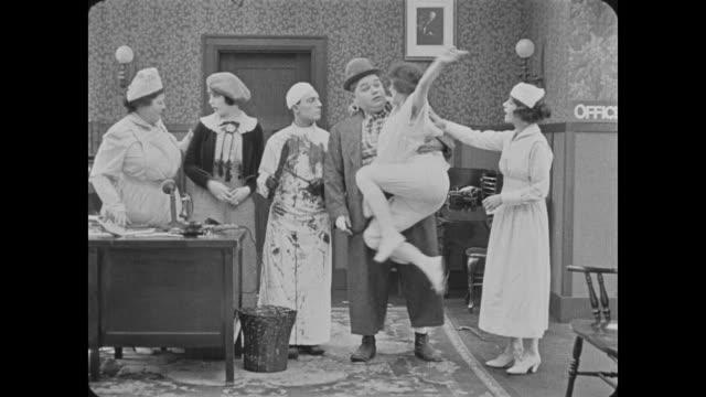 vídeos de stock e filmes b-roll de 1918 man (fatty arbuckle) being admitted to sanatorium kissed by crazy woman (alice lake) - andar em bico de pés