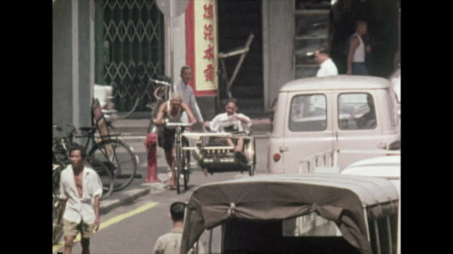 vídeos y material grabado en eventos de stock de man being driven in a rickshaw in singapore; 1972 - bicicleta antigua