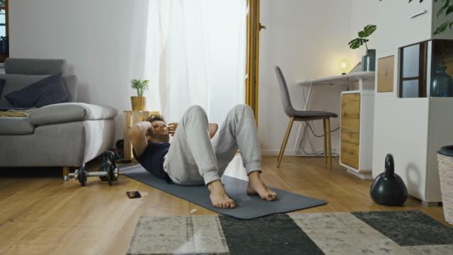 vidéos et rushes de ds homme étant épuisé après avoir fait l'exercice intense à la maison - s'étirer