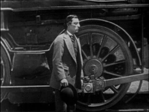 stockvideo's en b-roll-footage met b/w 1927 man being rejected by woman in front of train / 1860s / feature - 1927