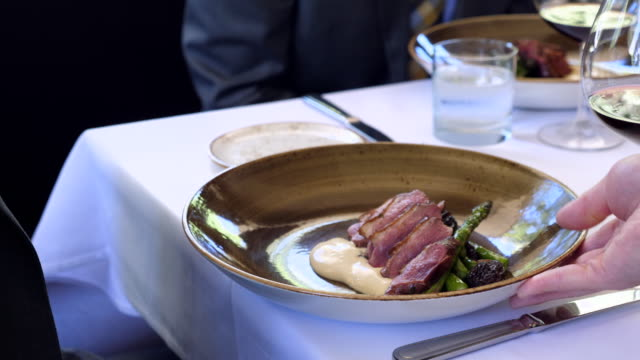 ms man being served plate of roasted duck organic asparagus and morels - plate stock videos & royalty-free footage
