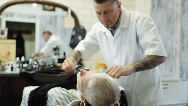 man being shaved with straight razor in front of mirror - shaving brush stock videos & royalty-free footage