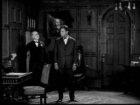 1924 b&w ws man being shown to fancy room by butler  - collaboratore domestico video stock e b–roll