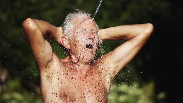 stockvideo's en b-roll-footage met cu man being watered in garden / corsept, loire-atlantique, france - alleen één seniore man