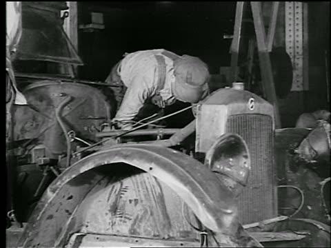 b/w 1930 man bending over taking car apart for scrap metal / newsreel - 1930 stock videos & royalty-free footage
