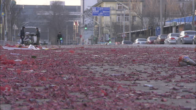 a man bicycles through red petals covering a street after a festival in beijing. - 2010年代点の映像素材/bロール
