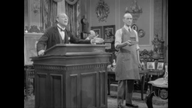 1946 man bids on music box at art auction - せり売り点の映像素材/bロール