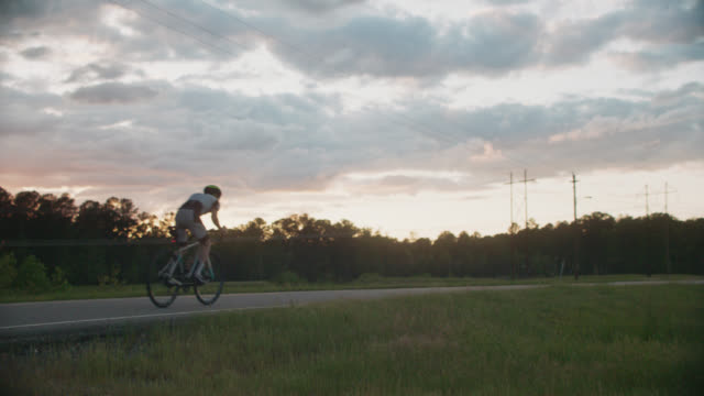 man bikes past nuclear power station along an empty road - power line stock videos & royalty-free footage
