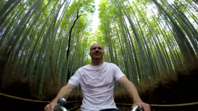 man biking through a bamboo forest - kyoto stock videos and b-roll footage