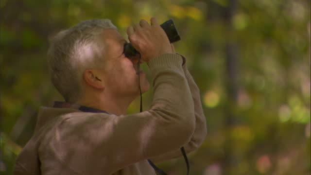 MS PAN man birdwatching with binoculars/ Livingston, New York