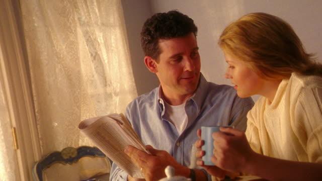 stockvideo's en b-roll-footage met ms man + blonde woman at breakfast table talking + looking at stocks page of newspaper together - financiële pagina