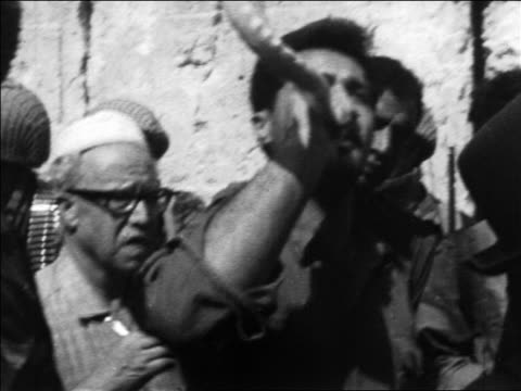 vidéos et rushes de b/w 1967 man blowing shofar in crowd at wailing wall after six day war / jerusalem / newsreel - 1967