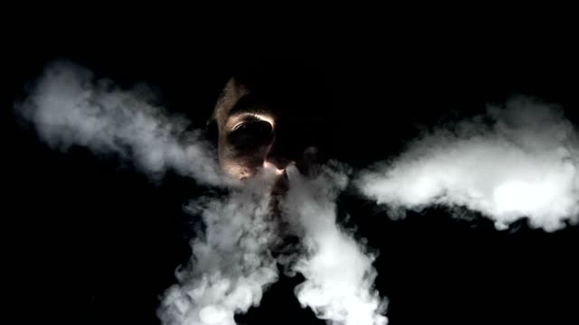 slo mo man blowing smoke through his nose and mouth - back lit stock videos & royalty-free footage