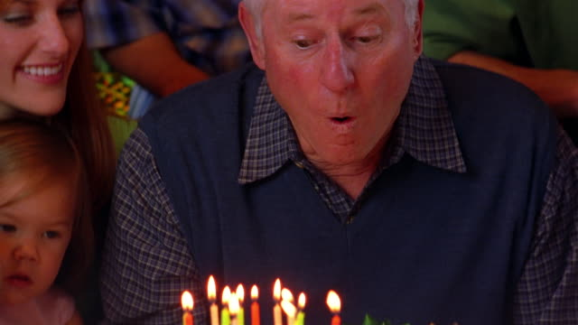 a man blows out candles during a birthday party. - birthday stock videos and b-roll footage