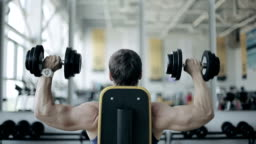 Man bodybuilder execute exercise with dumbbells in gym