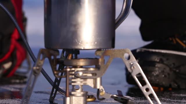 man boils water from snow on a gas burner. - キャンプ用ストーブ点の映像素材/bロール