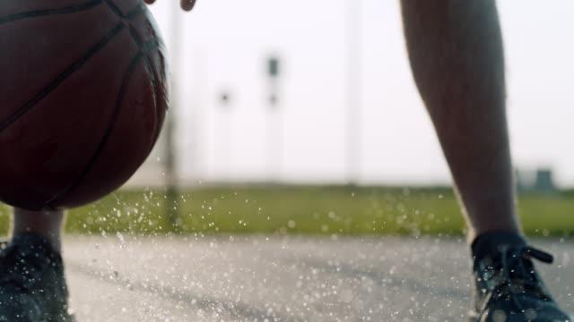 cu super slow motion mann hüpft und spritzt basketball in wasserpfütze - nah stock-videos und b-roll-filmmaterial