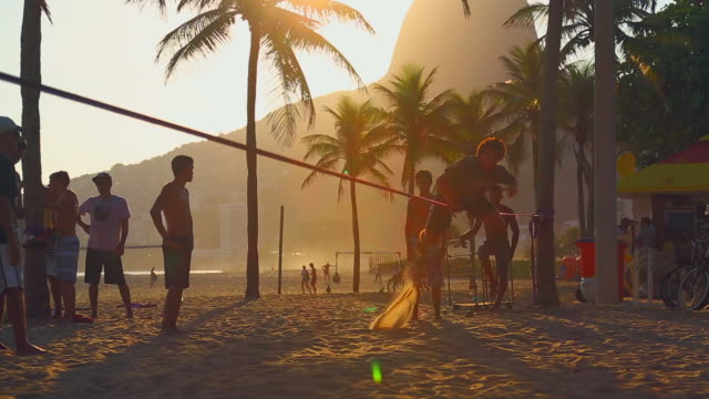 stockvideo's en b-roll-footage met man bouncing on slackline on beach at sunset - agressie