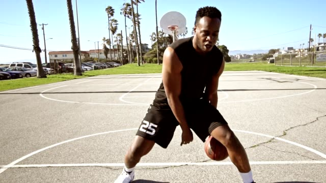 man bouncing the ball in a street basketball court - agility stock videos & royalty-free footage