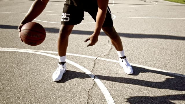 man bouncing the ball in a street basketball court - shorts stock videos & royalty-free footage