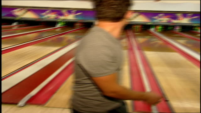 man bowling with neon bowling ball toward neon pins - bowling ball stock videos & royalty-free footage