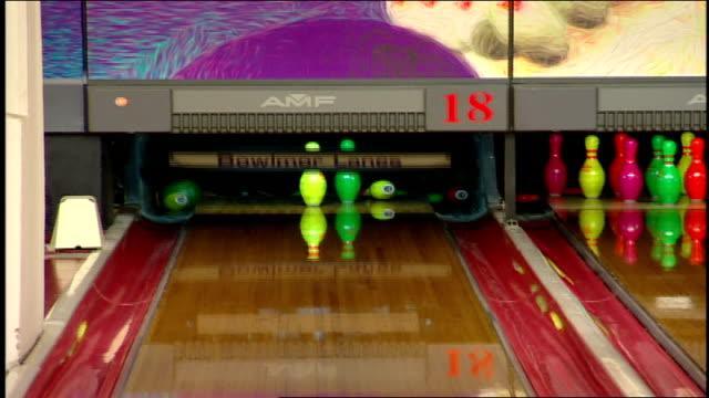 man bowling with neon green bowling ball toward neon pins - bowling ball stock videos & royalty-free footage