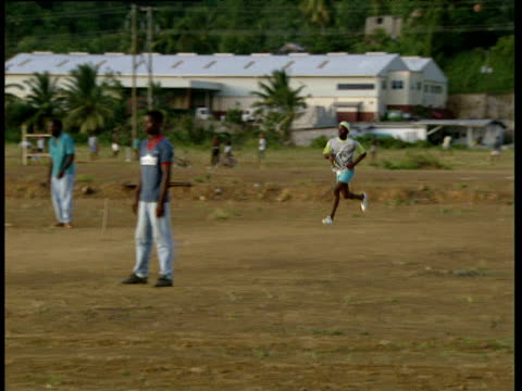 man bowls at speed during game of cricket windward islands - cricket video stock e b–roll