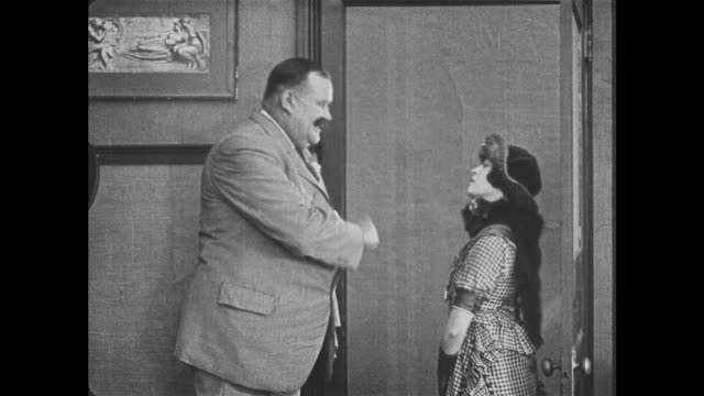 1921 man (joe roberts) bows in greeting to a dismissive woman (virginia fox) on her way out - 1921年点の映像素材/bロール